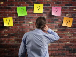Choice and decisions businessman thinking with question marks written on adhesive notes stuck to a brick wall